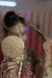 Indian Hindu Bride with jewelry looking in mirror. Stock Photos