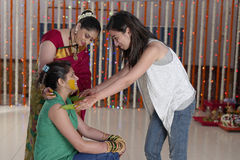 Indian Hindu Bride with turmeric paste on face with sister and mother. Stock Photo