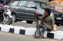 Indian Hindu man beg or seek help on busy road Stock Photo