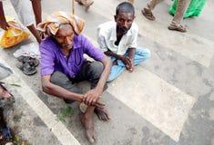 Indian Hindu men beg or seek help on busy road Royalty Free Stock Images