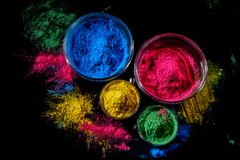 Indian Holi festival colours in four bowls on dark background. stock photography