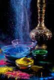 Indian Holi festival colours. Several bowls with Holi paint powder. Explosion of blue color. Indian lipped jug. stock image