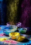 Indian Holi festival colours. Several bowls with Holi paint powder. Explosion of purple, yellow and blue color. Indian Holi festival colours. Several bowls with stock photography