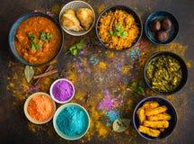 Indian Holi food. Traditional assorted Indian food, Holi colours powder, rustic background. Indian Holi holiday. Indian dishes and snacks set. Holi celebration Royalty Free Stock Image