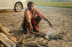 Indian homeless man sits beside a fire to keep warm on a cold winter morning. Stock Photo