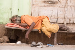 Indian homeless man sleeps near the ghat along the sacred Sarovar lake royalty free stock photography