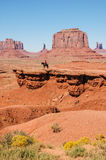 An Indian on a horse in front of a red rock, USA Royalty Free Stock Image