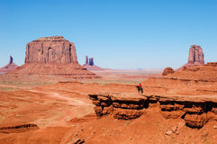 An Indian on a horse in front of a red rock, USA Stock Photos
