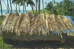 Indian hut on seafront, covered with plastic, palm leaves and fishing net. Stock Images