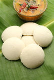 Indian idli sambar. Indian idli with sambar on a banana leaf Royalty Free Stock Image