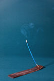 Indian incense. Blue Indian incense stick on a wooden stand burning with smoke Stock Images