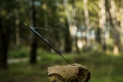 Indian incense lit smoking stick against the forest. Blurred texture royalty free stock photography