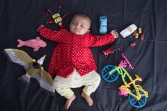 Indian Infant baby sleeping with toys. Asian Indian Infant baby sleeping with many toys cycle, car, bird, fish, puppet stock photo