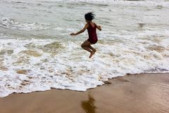 Indian kid girl jumping against approaching wave on puri sandy beach in seashore expressing joy and excitement stock photography