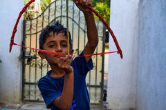 Indian kid playing with his bow and arrow in home stock image