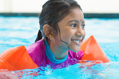 Indian kid swimming. Indian girl learning swimming in pool. Asian child in swimmer class with float bands Stock Photography