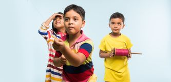 3 indian kids flying kite, one holding spindal or chakri Royalty Free Stock Image