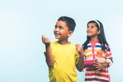 2 indian kids flying kite, one holding spindal or chakri Royalty Free Stock Photography