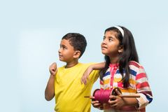 2 indian kids flying kite, one holding spindal or chakri Stock Image