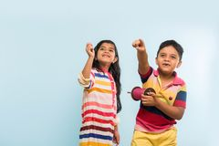 2 indian kids flying kite, one holding spindal or chakri Stock Photos