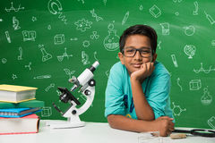 Indian kids and science. Kids and science concept - cute indian little kids studying science and using microscope with diagrams or doodles drawn over green royalty free stock image