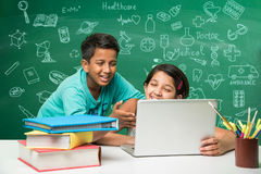 Indian kids and science. Kids and science concept - cute indian little kids studying science and using microscope with diagrams or doodles drawn over green stock photos