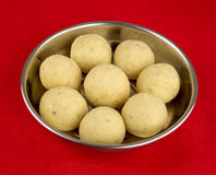 Indian laddoo treats in a silver plate against red tablecloth Royalty Free Stock Photography