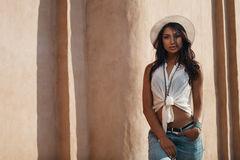 Indian lady in casual summer outfit against ancient building. Stock Photos