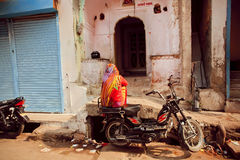 Indian lady sitting on motorbike on poor people area of old city Stock Images
