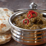 Indian Lamb Korma. Curry in traditional copper bowl, with naan bread Stock Photo