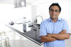 Indian latin man interior modern kitchen white Royalty Free Stock Images