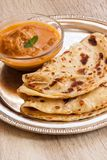 Indian layered Paratha flat bread. Indian layered Paratha roti kerala porotta with chicken curry on the side Stock Photography