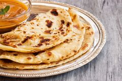 Indian layered Paratha flat bread. Indian layered Paratha roti kerala porotta with chicken curry on the side Royalty Free Stock Photography