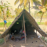 Indian life. Primitive village smithy in palm tree grove and blacksmiths with tools stock photo