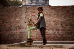Indian little girl  on  hand-pump Royalty Free Stock Image