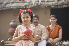 Indian little girl holding piggy bank in front of parents royalty free stock photos
