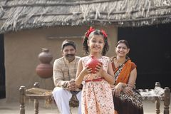 Indian little girl holding piggy bank in front of parents royalty free stock image