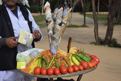 Indian local Chat with tomato and green chilly. An Indian Man selling desi chaat with tomato and green chilly stock images