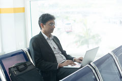Indian male business man working from airport terminal Royalty Free Stock Images