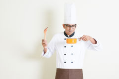 Indian male chef in uniform cooking and enjoy the food aroma Stock Images