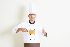 Indian male chef in uniform cooking and thumb up Royalty Free Stock Image
