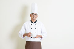 Indian male chef in uniform holding a coffee cup Royalty Free Stock Photography
