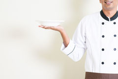 Indian male chef in uniform holding an empty plate Royalty Free Stock Photos