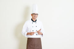 Indian male chef in uniform holding kitchen tool Royalty Free Stock Photos