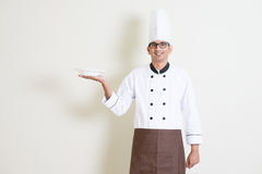 Indian male chef in uniform holding a plate Royalty Free Stock Photography