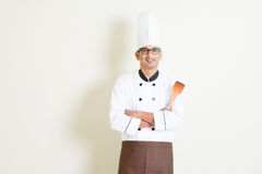 Indian male chef in uniform holding spatula Stock Photo