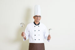 Indian male chef in uniform with kitchen tools Stock Photos