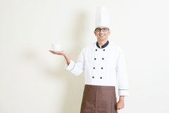 Indian male chef in uniform presenting a coffee cup Royalty Free Stock Image