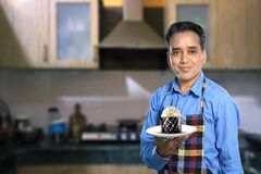 Free Indian Male Chef With A Sweet Dish In Kitchen Interiors Royalty Free Stock Images - 176820449