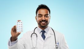 Indian male doctor with pills and stethoscope. Medicine, profession and healthcare concept - smiling indian male doctor in white coat with pills and stethoscope royalty free stock photography